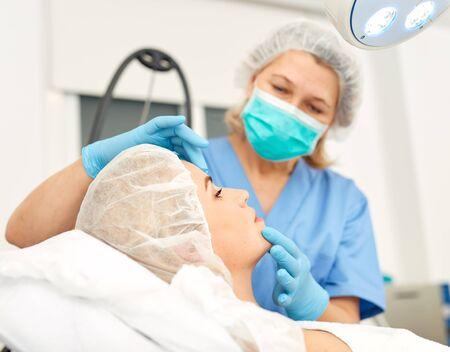 Doctor is examining woman patient before the procedure 写真素材