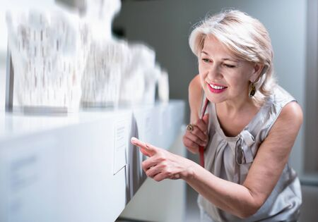 Positive glad cheerful smiling woman in art museum near the antique classical sculpture Stock Photo