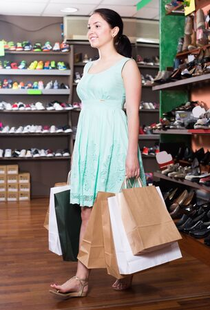 Elegant female customer is showing her purchases in shoes shop 版權商用圖片