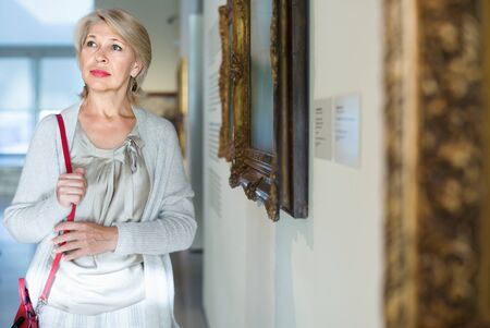 Glad cheerful  smiling mature woman standing in art museum near the painting in baguette Stock Photo