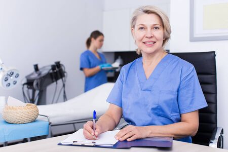 Mature female doctor cosmetologist working with documents in modern cosmetic office 写真素材