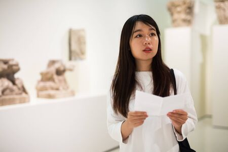 Portrait of chinese girl holding guidebook, standing in museum of ancient sculpture