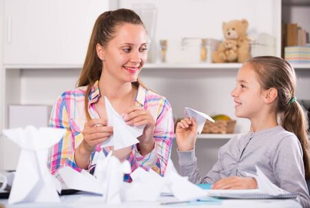 Cheerful female playing with schoolgirl in origami sitting at the table