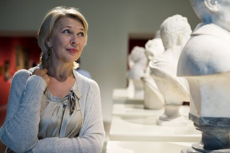 Adult female looking at artwork sculpture in the museum indoors