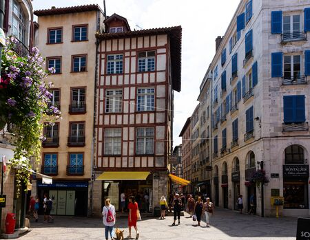 BAYONNE, FRANCE - JULY 17, 2019: Traditional Basque architecture of Bayonne streets. View of half-timbered houses on narrow street in French town Sajtókép