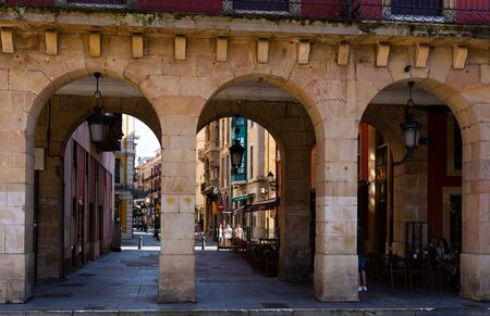 GIJON, SPAIN - JULY 15, 2019: View through archway of pedestrian street with people strolling in sunny summer day