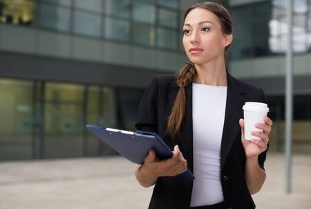 Businesswoman is examining documents and drinking coffee near office.