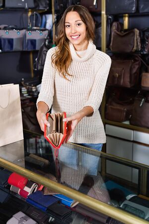 Portrait of glad beautiful  smiling woman selling wallets and purses in store Stockfoto