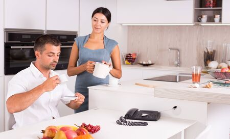 Smiling young woman with her husband having breakfast together at home