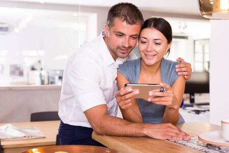 Loving couple spending time together, watching media in smartphone in comfortable kitchen