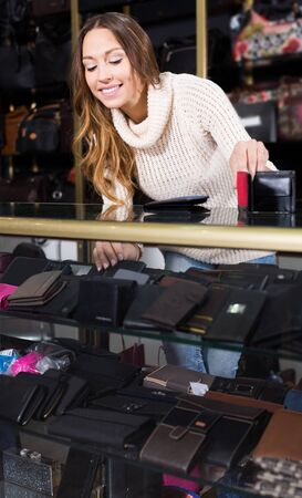 Young female shop assistand posing near glass display in wallet section