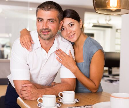 Portrait of happy young couple enjoying time together in kitchen of their house
