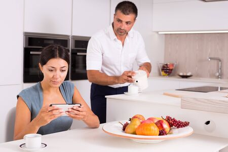 Young woman absorbed in her smartphone while husband pouring tea in home kitchen