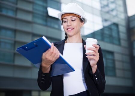 Smiling woman architector in suit and hat is exploring documents with project and drinking coffee near the building.
