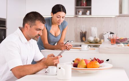 Young modern couple absorbed in theirs phones in kitchen interior