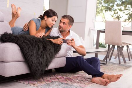 Portrait of happy young couple enjoying time together at home, watching media in smartphone Stock Photo