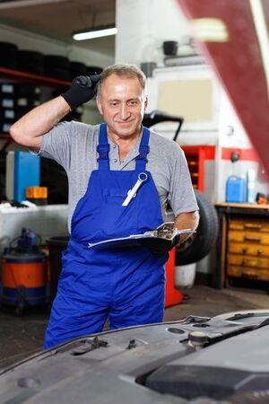 Skilled glad cheerful positive mature male mechanic taking notes in notebook about car repair at auto service