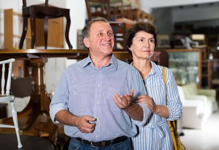 Portrait of cheerful mature woman with her husband who are satisfied of buying furniture in antique store