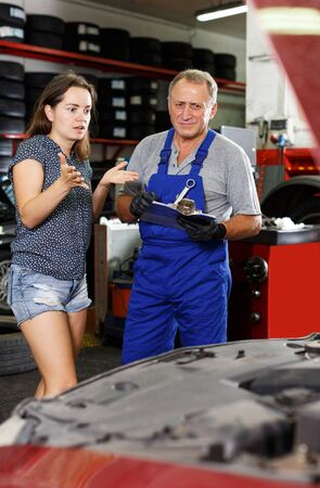 Worried young client of auto repair shop emotionally talking to elderly man mechanic about her car