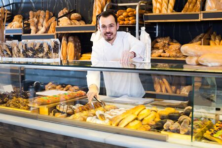 positive russian male shop assistant demonstrating fresh delicious pastry in bakery