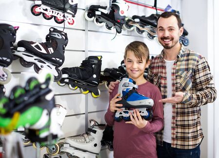 happy european male shop assistant helping boy to choose roller-skates in sports store