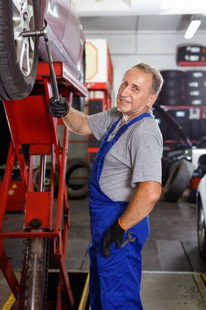 Elderly cheerful  man mechanic engaged in replacement of car wheel in auto workshop