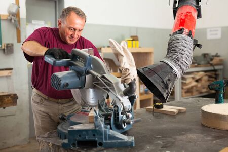 Confident workman cutting wooden planks using circular saw