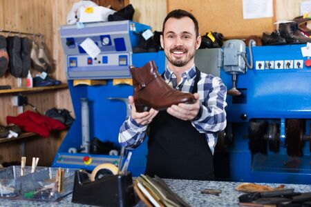 Young smiling friendly male worker demonstrating repaired shoes in shoe repair workshop