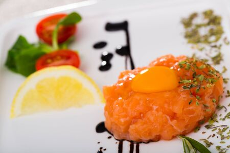 Tartare of fresh salmon on white plate. Recipe: finely chop 200 gr of fish, season with salt, black pepper, olive oil, lemon juice, garnish with yolk of quail egg, greens and balsamic vinegar
