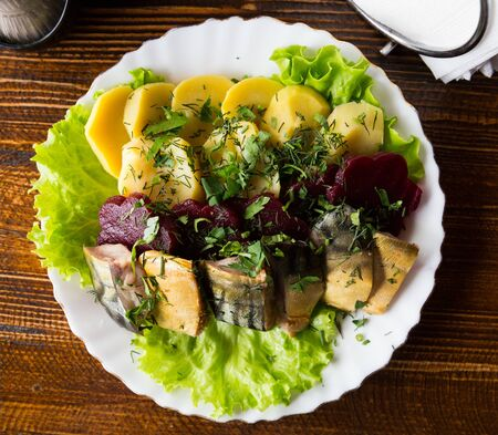 Top view of traditional Russian appetizer of sliced smoked mackerel served on lettuce leaves with boiled potatoes and beetroot on wooden background