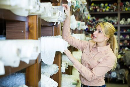 Positive attractive girl choosing fabric among diversity on shelves in store