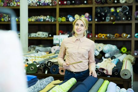 Portrait of positive salesgirl working in fabric store, demonstrating wide range of stylish cloth