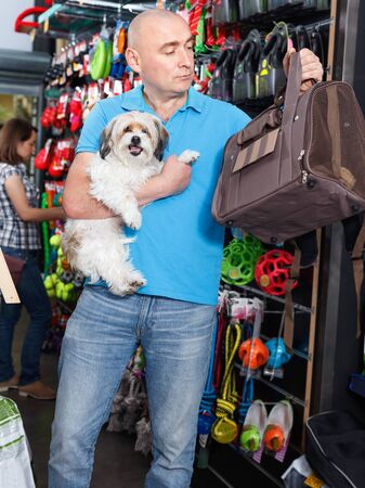 Portrait of  positive  young man  with small dog standing  in pet store
