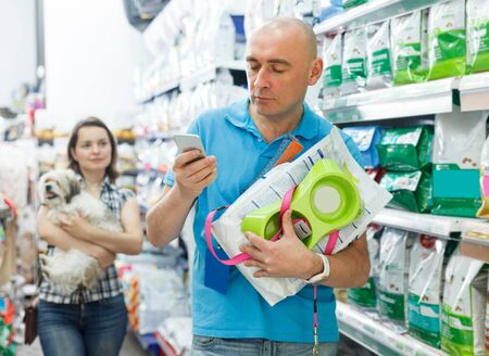 man with purchases dials a number in the phone in pet store, woman on background Banco de Imagens