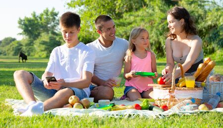 Interested teen boy playing on smartphone during picnic with his family on green meadow
