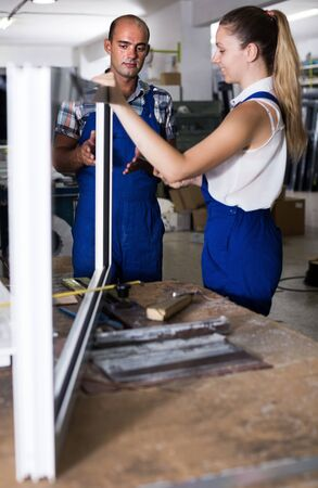Two positive workers in blue overalls assembling pvc windows at factory