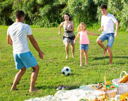 Happy friendly family with children playing football on green lawn in summer city park Stockfoto