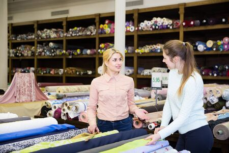 Polite female seller helping young woman in choice of interesting cloth in textile shop Imagens