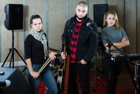 Expressive active adult group of rock musicians posing with instruments in recording studio Stock Photo