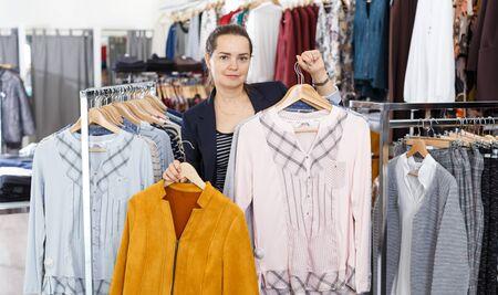 Giovane donna attraente che tiene poche grucce con i vestiti nel negozio di abbigliamento