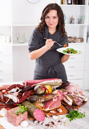 Slender woman chooses healthy food, but not sausages and smoked meat Stock Photo