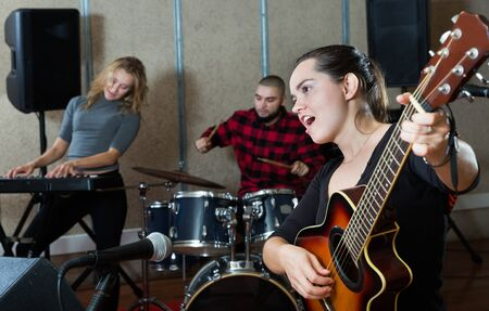 Portrait of excited adult girl rock singer with guitar during rehearsal with male drummer and female keyboardist in studio