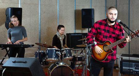 Repetitie van muziekband. Gelukkig vrolijke kerel gitarist en zanger oefenen met bandleden in opnamestudio Stockfoto