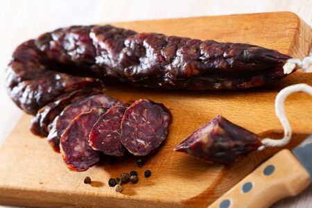 Traditional French  slicing dry-cured sausage with liver served on wooden board