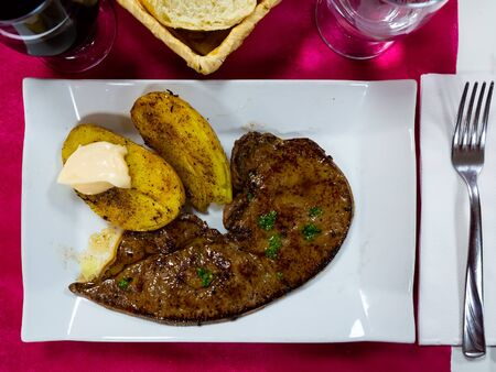 Roast veal liver with potatoes on a white plate Imagens