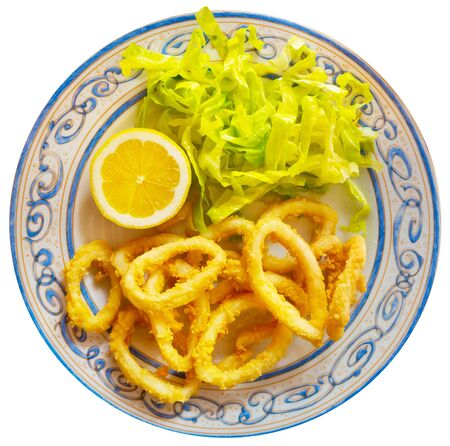 Fried calamari  in a batter of tempera flour and fresh salad with lemon. Isolated over white background