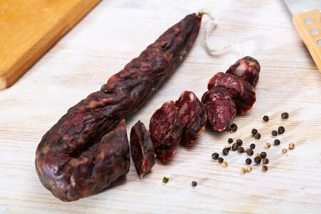 Spicy dry cured sausage with liver from on wooden background. Traditional French meat products Imagens