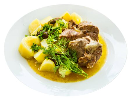 Stewed  tasty lamb with mushrooms and potatoes served at plate with greens. Isolated over white background
