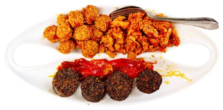 Traditional hot Spanish tapa of blood sausage, chorizo, picadillo and roasted peppers. Isolated over white background