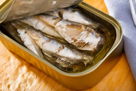 Open can of sardines preserves in oil on wooden table Stock Photo